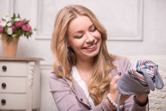 Young attractive woman holding baby hat , interior Royalty Free Stock Photo