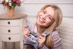 Young attractive woman holding baby hat , interior Royalty Free Stock Photography