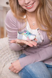Young attractive woman holding baby shoe, interior Royalty Free Stock Photography