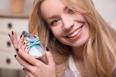 Young attractive woman holding baby shoe, interior Stock Photography