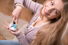 Young attractive woman holding baby shoe, interior Royalty Free Stock Photo