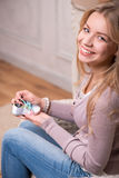 Young attractive woman holding baby shoe, interior Royalty Free Stock Images