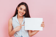 Young attractive woman holding blank billboard with copy space. And pointing finger over pink background Stock Photos