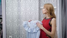 Young attractive woman is holding blue trendy dress and looking on it , standing in a fitting room of shop, closing. Curtain and smiling playfully stock video footage