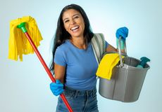 Young attractive woman holding cleaning tools and products in bucket on blue background royalty free stock photo