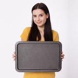 Young attractive woman holding an empty tray on white background. Royalty Free Stock Photography