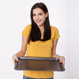 Young attractive woman holding an empty tray on white background. Stock Photography