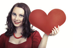 Young attractive woman holding heart and smiling. Holiday and valentine's day concept. Young attractive woman holding heart and smiling in red dress  isolated on Royalty Free Stock Images