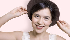Young attractive woman holding her hat and smiling Royalty Free Stock Image
