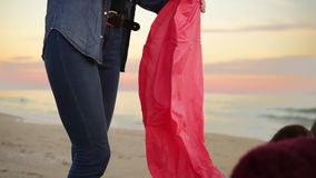 Young attractive woman holding lantern with fire before letting it fly standing by the beach together with her friends. Friends having fun at the beach during stock video