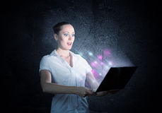 Young attractive woman holding a laptop. It shines and depart monitor lights royalty free stock images