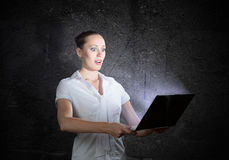 Young attractive woman holding a laptop. It shines and depart monitor lights stock photography