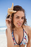 Young attractive woman holding a starfish next to her head Royalty Free Stock Photos