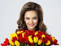 Young attractive woman holds the red and yellow tulips Royalty Free Stock Images