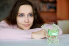 A young attractive woman with a hope and enthusiasm dreamily looks ahead to the future. A green pram toy. The stroller in the foreground, a woman in the blur royalty free stock photos