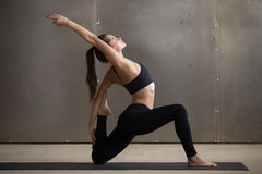 Young attractive woman in Horse rider pose grey studio backgroun. Young attractive woman practicing yoga, standing in Horse rider exercise, anjaneyasana pose stock photography