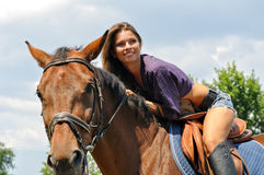 Young attractive woman horseback riding. In the summer sunny day Stock Images