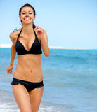 Beach jogging. Young attractive woman jogging on the beach royalty free stock images