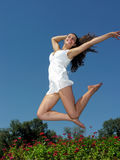 Young attractive woman jumping over summer flowers. In sunny day Royalty Free Stock Images