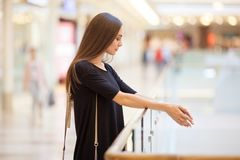 Young attractive woman in large mall in black dress and with sho. Pping bags. Sale and business concept Royalty Free Stock Photo