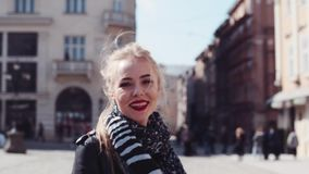 Young attractive woman in a leather jacket, with red lips and blonde ponytail walking in the city center, turns to stock video footage