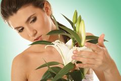 A young and attractive woman with a lily flower Royalty Free Stock Photo