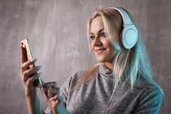 Young and attractive woman listening to music in the mobile app. Girl music lover. stock photos