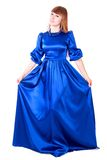 Young attractive woman in a long blue evening dress. Isolated over white background Royalty Free Stock Photo