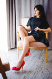 Young attractive woman with long legs in black elegant dress, sits in chair near window in interior of room. Seductive shoes of red light, on beautiful legs royalty free stock images