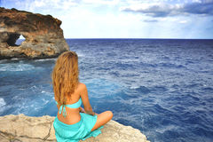 Young attractive woman looking at sea horizon sitting alone on r. Ock cliff in cyan glamour dress under a summer blue sky in relax , meditation and serenity Stock Images