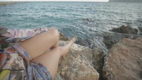 Young attractive woman looking at sunset sun sitting on a rocky sea shore. The hair fluttering in the wind. Dolly out stock video