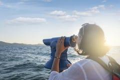 Young woman looks in a telescope or binoculars by the sea. Young attractive woman looks in a telescope or binoculars by the sea Stock Photography