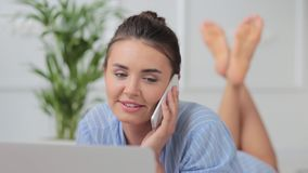 Young attractive woman lying on bed with laptop and talking on the phone stock footage