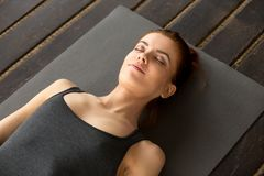 Young attractive woman lying in Dead Body exercise. Or Corpse pose with her eyes closed, Savasana pose, working out, resting after practice, indoor close up Royalty Free Stock Photos