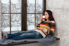 Young attractive woman lying down on the pillows on the windowsi Stock Image