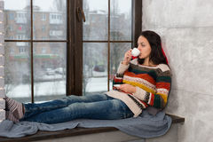 Young attractive woman lying down on the pillows on the windowsi Royalty Free Stock Images