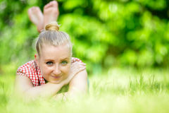 Young attractive woman lying on grass. Stock Image