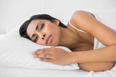 Young attractive woman lying on her bed wrinkling her brow. Looking at camera Stock Images
