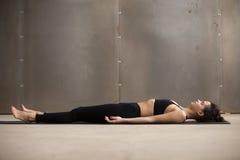 Young attractive woman lying in Savasana pose, grey studio backg Royalty Free Stock Photos