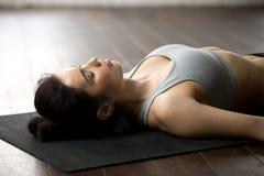 Young attractive woman lying in Savasana pose, white loft studio Stock Photography