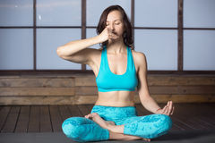 Young attractive woman making Alternate Nostril Breathing, studi. Young attractive woman practicing yoga, sitting in Half Lotus pose, making Alternate Nostril Stock Images