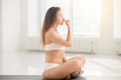 Young attractive woman making Alternate Nostril Breathing, white. Young lady practicing yoga, sitting in Easy Seat pose, making Alternate Nostril Breathing stock photo