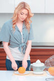 Young attractive woman making fresh juice Stock Photo