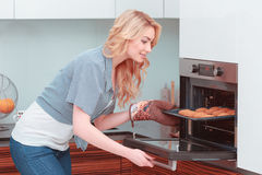 Young attractive woman making home pastry. Baking day. Young beautiful woman putting a tray of home pastry in the oven Royalty Free Stock Photography
