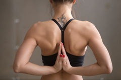 Young attractive woman making Namaste behind the back, grey stud stock photography