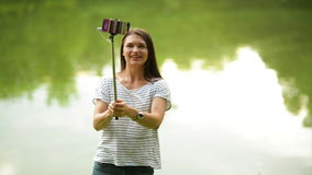 Young attractive woman is making photo with selfie stick near the lake. Smiling brunette is using her smartphone stock footage