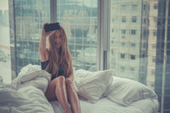Young attractive woman making self portrait in the bed in the morning Stock Image