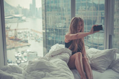 Young attractive woman making self portrait in the bed in the morning Stock Photography