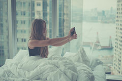 Young attractive woman making selfie in the bed Stock Images