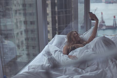 Young attractive woman making selfie in the bed Stock Photography